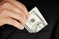 Mid section view of a businessman putting dollar bills in his pocket
