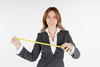 Portrait of a businesswoman holding a measuring tape and smiling