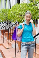 Teenage girl standing on steps and talking on a mobile phone
