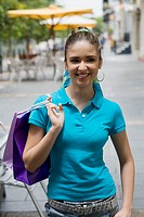Close-up of a teenage girl holding shopping bags and smiling