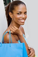 Portrait of a teenage girl holding a shopping bag and smiling