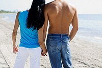 Rear view of a man and a woman holding hands on the beach