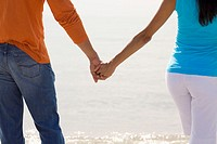 Mid section view of a young couple standing on the beach and holding hands (thumbnail)