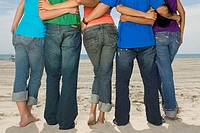 Rear view of five people standing on the beach