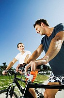 Low angle view of two young men on bicycles