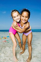 Portrait of two girls hugging each other on the beach