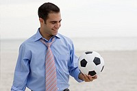 Close-up of a young man standing on the beach and holding a soccer ball
