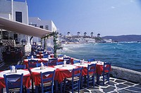 Empty chairs with tables in a restaurant by the sea