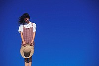 Low angle view of a young woman holding a sun hat