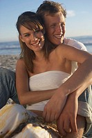 Teenage couple (15-19) embracing on beach, smiling