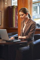 Young businesswoman at cafe table, using laptop computer
