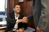 Young businessman at cafe table, shaking another businesman´s hand