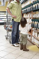 Girl (3-5) infront of spill in supermarkte, looking at father