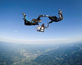 Three skydivers holding hands during freefall, aerial view