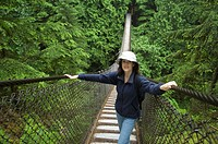 Woman standing on suspension bridge in forest, portrait