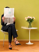 Businesswoman reading newspaper beside table with flowers in vase