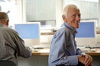 Senior man in computing class, looking around, smiling, portrait