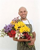 Man holding bunch of flowers, smiling, portrait