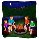 A family cooking sausages by the campfire at night