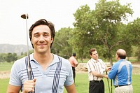 Four men on golf course, one holding golf club