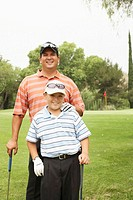 Father and son (8-10) on golf course