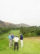 Four golfers talking on green