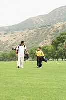 Father and son (8-10) walking on golf course