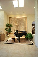 A piano is seen near an artistic painting in a deluxe house
