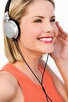 Woman wearing headphones, smiling, looking away