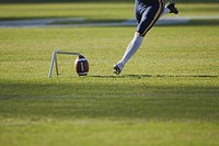 American football player, kicking ball, low section
