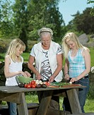Grandmother and grand daughters (11-15) preparing food outdoors