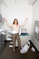 Businesswoman tossing papers in the air, portrait