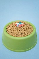 Pills on top of dog food in bowl