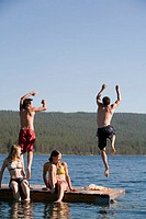 Four young adults on dock, women watching men jump into lake