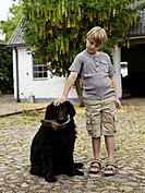 Young boy (7-8) with black dog in back yard