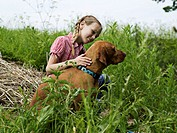 Girl (10-11) in long grass with brown dog, side view