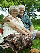 Senior couple sitting on garden bench, portrait