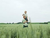 Father carrying son (8-9) on shoulder in a field