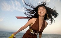 Happy girl Ella twirls at a beach in Southern california at dusk.