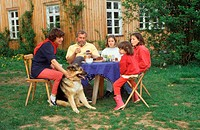 Family, with, Mixed, Breed, Dog, sitting, at, garden, table
