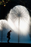 Young Man Walking Next to Fountain