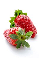 Two fresh, juicy strawberries with green tops