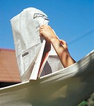 Hand holding newspaper in a hammock