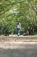 Young Asian woman walking dog in park