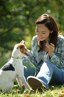 Young smiling Asian woman with pooch in park