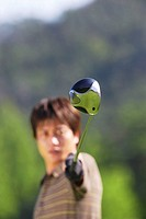 Asian golfer pointing club toward camera
