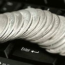 High angle view of antique Indian one rupee coins on a computer keyboard