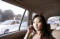 Portrait of a young woman talking on a mobile phone in a car