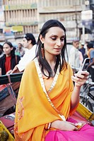 Young woman sitting in a rickshaw and using a mobile phone