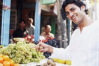 Portrait of a young man standing at a fruit stand
